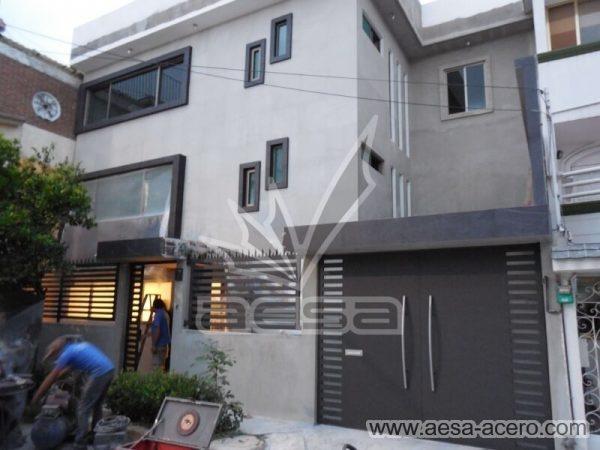 1040-116-porton-minimalista-rejilla-lateral-jaladeras-grandes-curvas-fachada