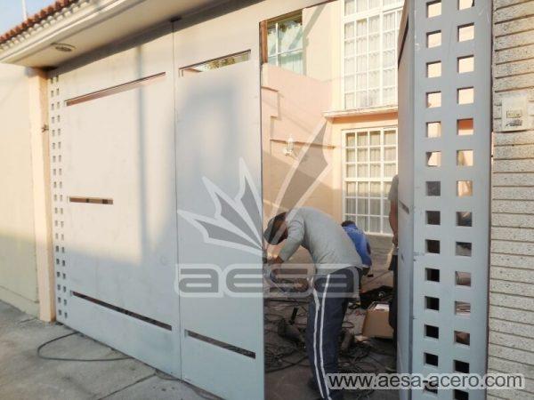 1090-117VG-porton-minimalista-vidrios-rectangulos-angostos-cuadricula-lateral-instalacion-chapa